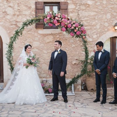bride & groom at ceremony arch at rustic villa wedding in Crete