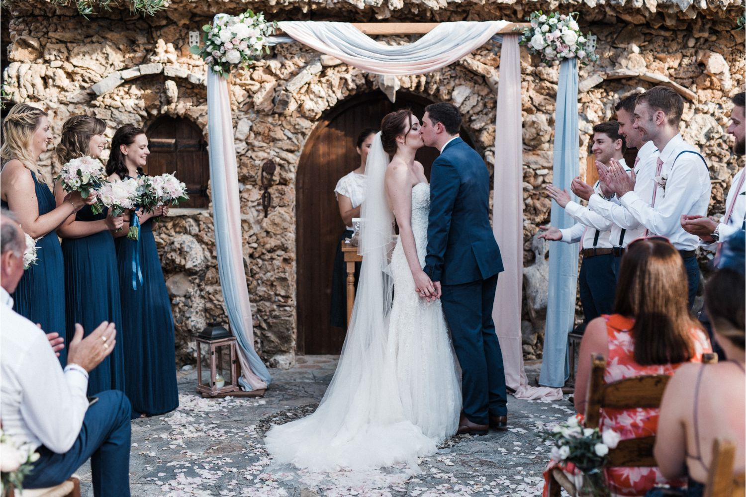 bride & groom kiss at rustic wedding ceremony in Crete